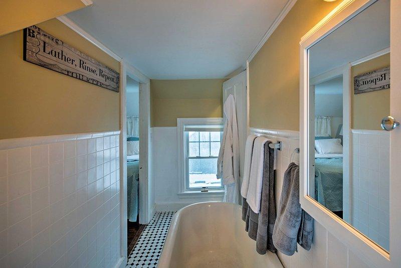 The jack-and-jill bathroom boasts a vintage clawfoot tub and pedestal sink atop checker-board flooring.