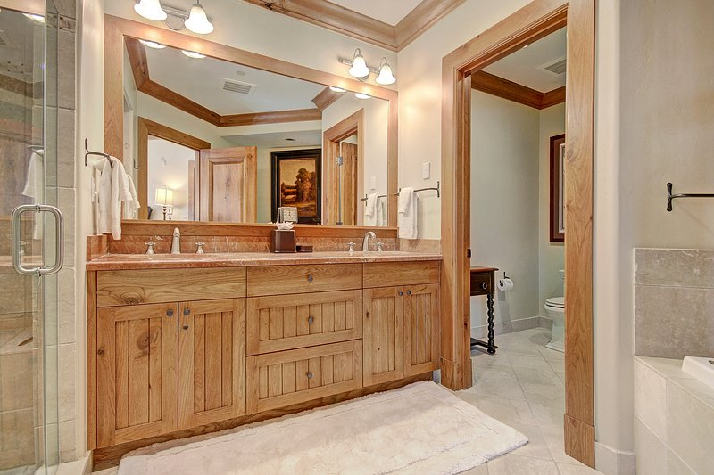 Master bathroom with double vanity, shower, and tub