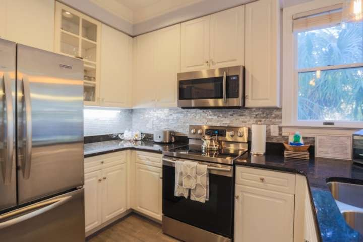 This newly renovated kitchen features stainless steel appliances, tiled backsplash and granite countertops.