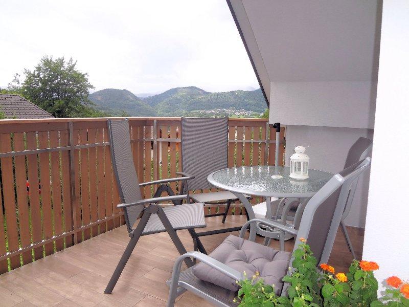 Ein großer Balkon mit Gartenmöbeln und schöner Aussicht.