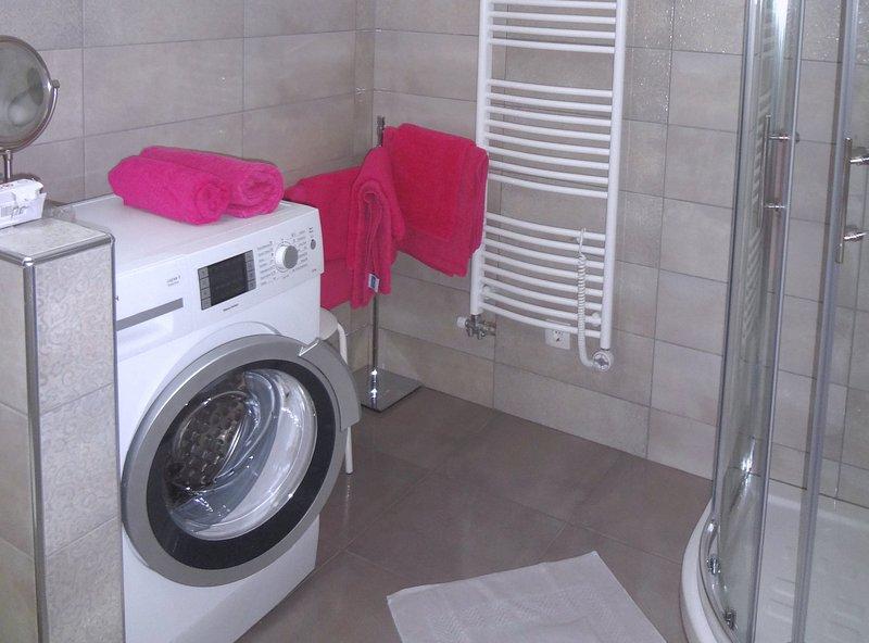 Ein Bad mit Duschkabine und Waschmaschine