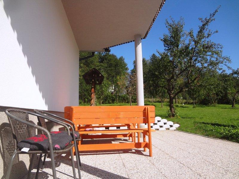 Eine Terrasse und ein Garten unter dem Balkon, die Gäste nutzen können