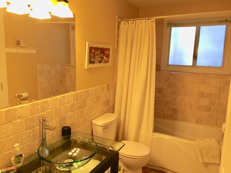 Stone tiled bathroom with soaker tub and shower and glass vanity and sink bowl