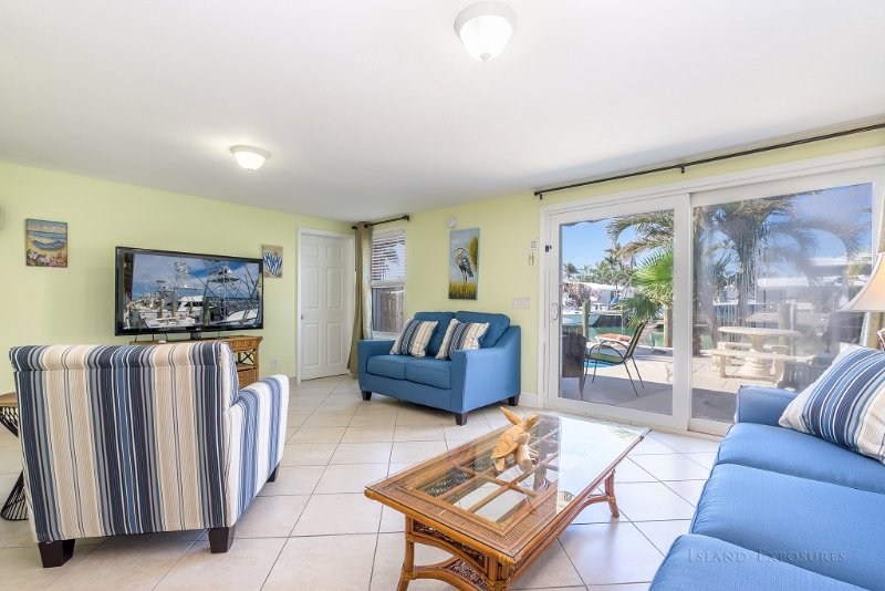 Living room with large 50' TV and view of pool and waterway canal.