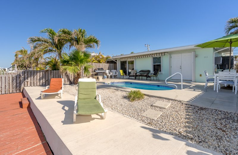 Wide view of View of pool, Dock, patio furniture, table for 6, gas grill and roll out auto 20x10.
