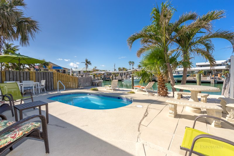 Beautiful view of our pool, palm trees, patio tables and many chairs. Gas Grill is on the right side