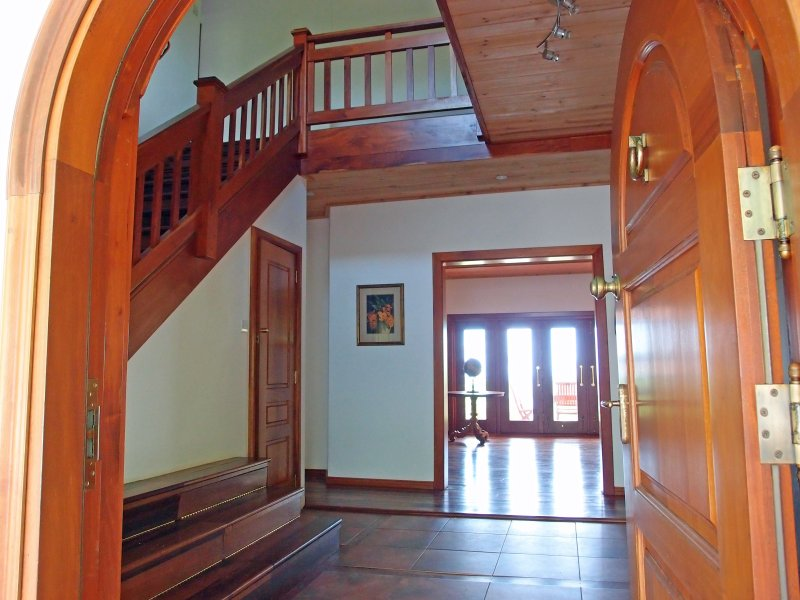 The arched front door opening to the hallway, powder room, living room and staircase..