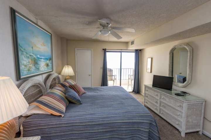 Master bedroom with king size bed, TV and direct balcony access.