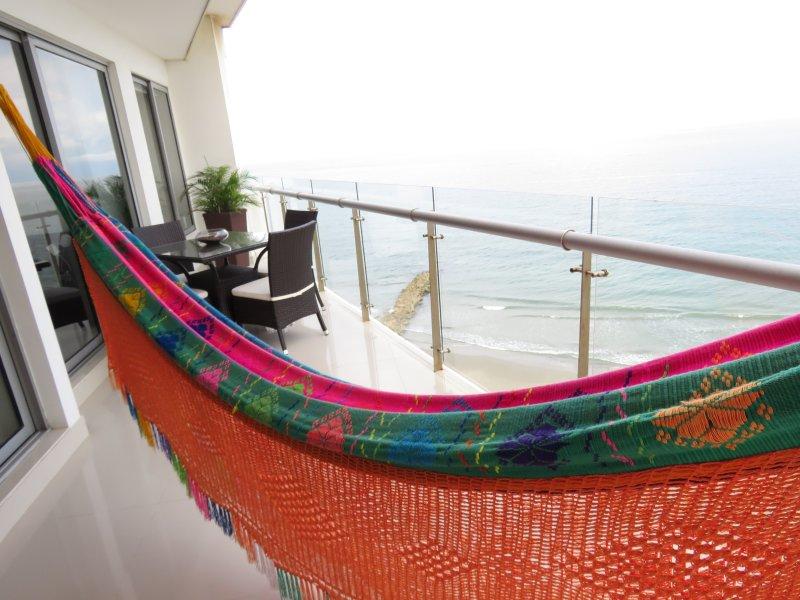 Hangmat en eethoek op het balkon met uitzicht op de oceaan / Hamaca en el balcón con vista al mar