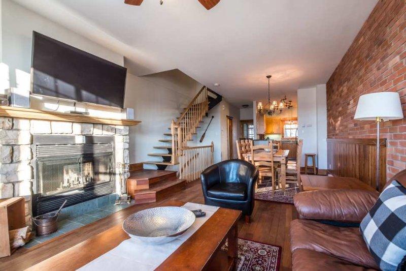 Sala de estar con ventanas grandes y una acogedora chimenea de piedra