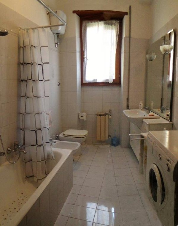 the large and bright bathroom has the washing machine