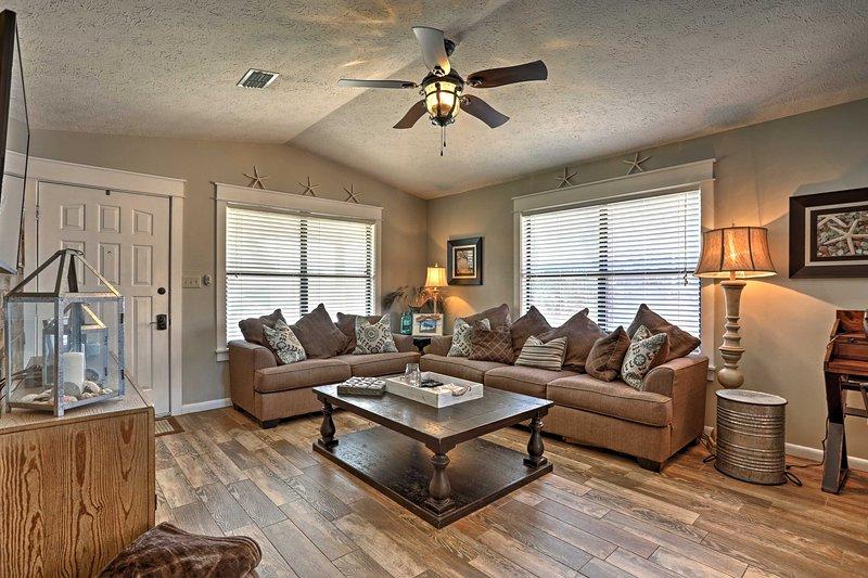 Lounge nella zona giorno aperta con un divano a forma di L e una Smart TV a schermo piatto da 55 pollici.