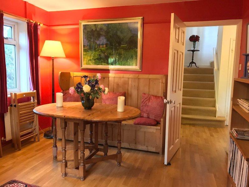 La mesa de comedor tiene capacidad para 6 personas cómodamente en la sala de estar roja.