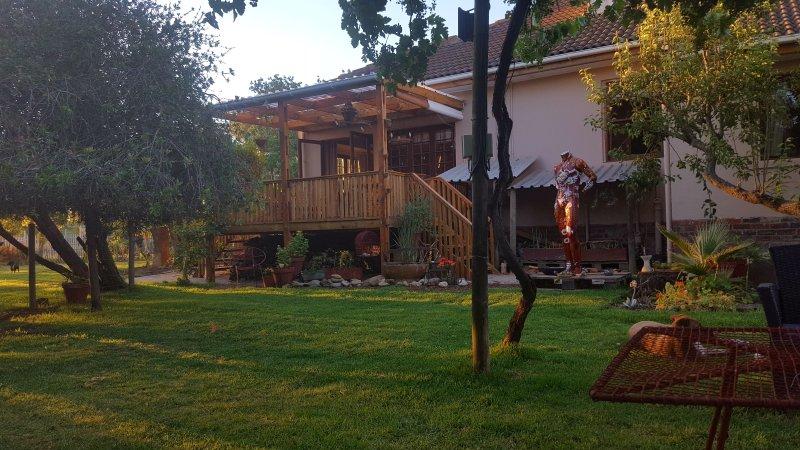The Cove espaçoso jardim e exuberante artístico com instalações de churrasco que conduzem para o convés adjacente.