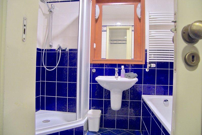 Casa de banho com canto chuveiro e banheira. Máquina de lavar roupa e secador.