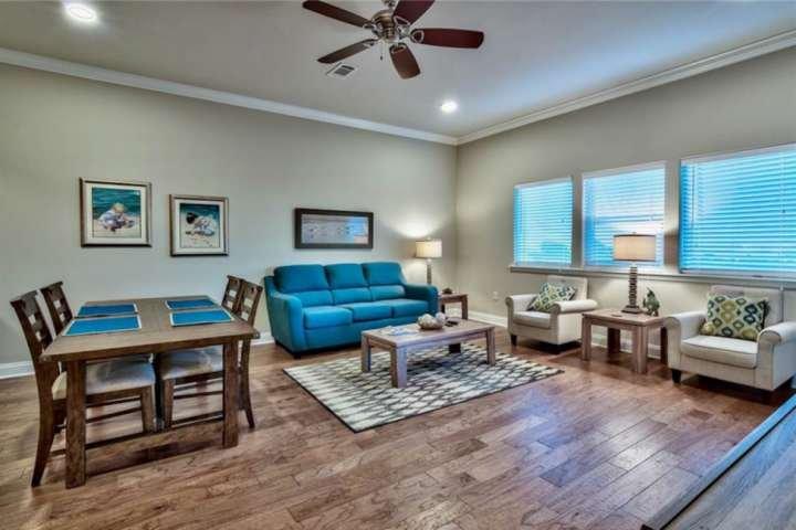Stort stort rum med trägolv, soffa, två sidostolar, tillfälliga bord och lampor och matbord för 4