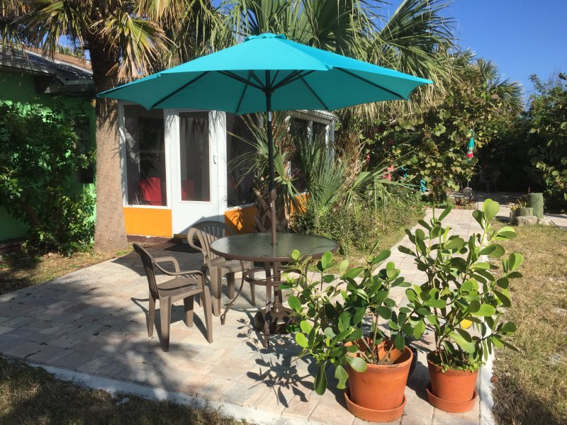 Side door to the screen porch and front patio with table and umbrella