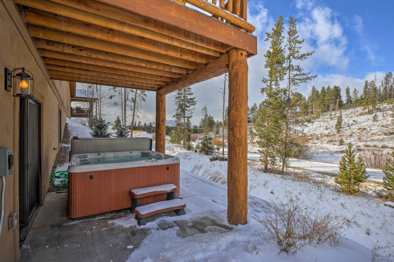 The home features a private hot tub and upper deck with mountain views.