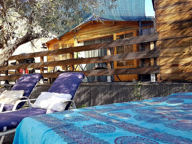 Outside area of cabin showing day bed, sun loungers and decked seating area