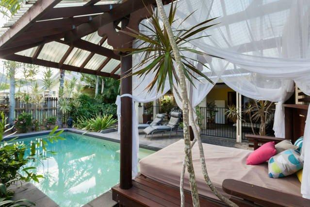 Ver a través de la piscina y sofá-cama a la gran área de entretenimiento y barbacoa
