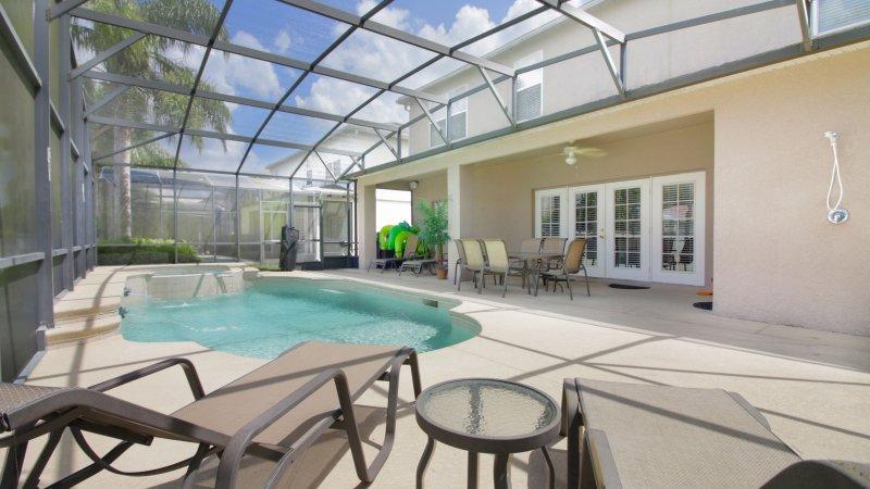 Aproveite o sol enquanto está sentado ao lado da grande piscina e spa