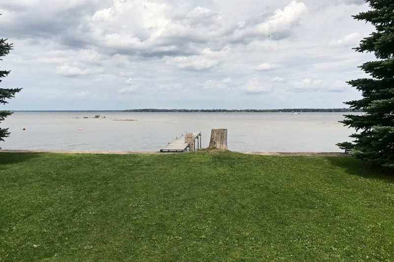 Lakefront views await at this 3-bedroom, 2-bath vacation rental in Prudenville!