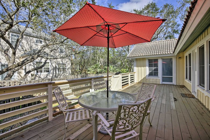 Relax on the furnished porch while birds flutter through the live oak trees.