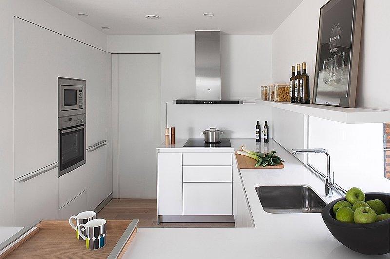 cocina completamente equipada con lavavajillas, lavadora, frigorífico, congelador, nevera para bebidas, horno y encimera