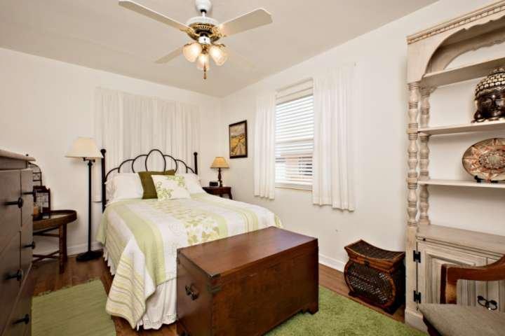 El segundo dormitorio cuenta con cama de matrimonio, un armario alto, ventilador de techo y despertador.
