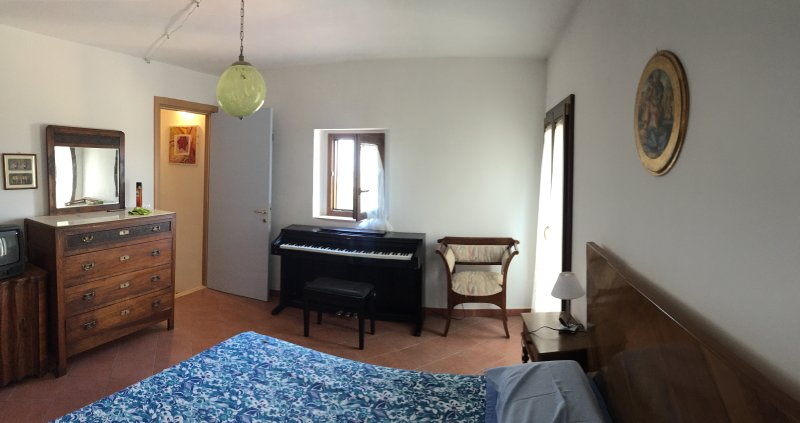 chambre au deuxième étage avec une fenêtre et un balcon donnant sur la place