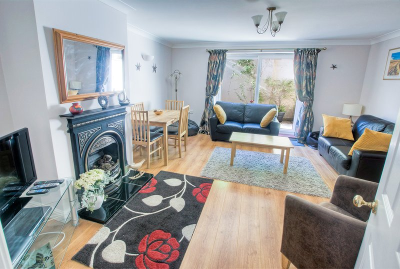 Annie's Cottage, lounge with dining table and chairs, patio door to enclosed patio.