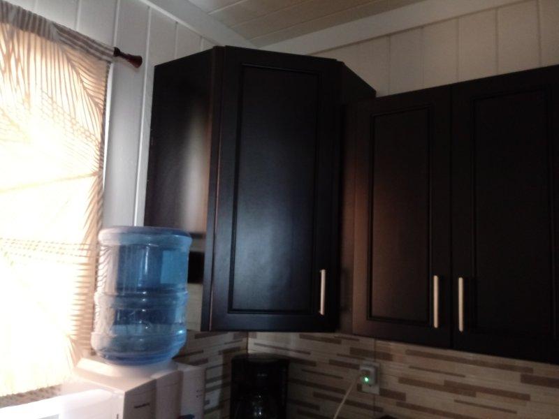 Watercooler e cafeteira localizado na cozinha.