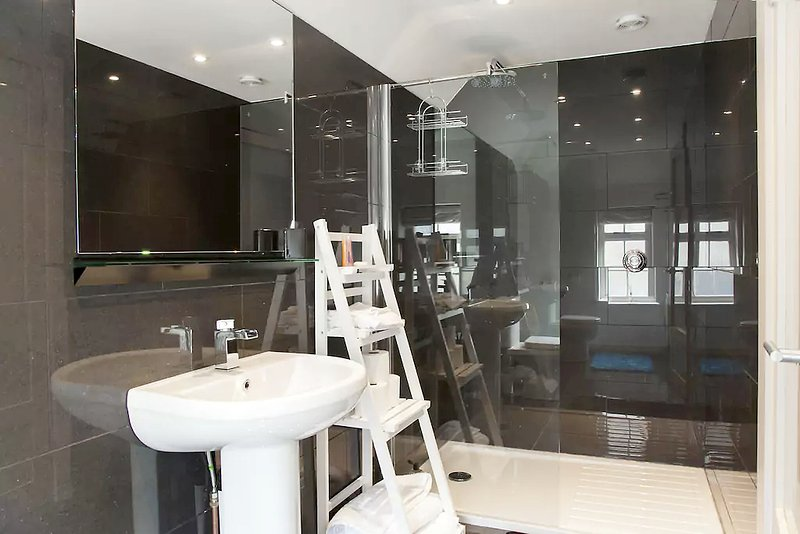 Fully tiled shower room with large digital shower, sink and toilet.