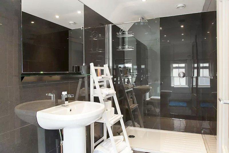 casa de banho totalmente revestidas com digital grande chuveiro, pia e vaso sanitário.