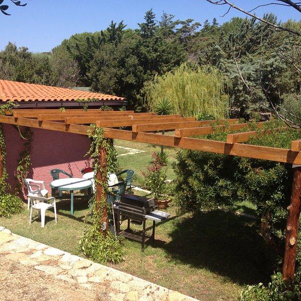Cottage, op het zuiden, grenzend veranda met gas grill, tafels, stoelen en hangmat