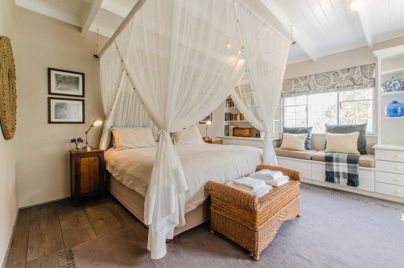 Chambre avec parquet en bois, vue sur un jardin de campagne d'itinérance.