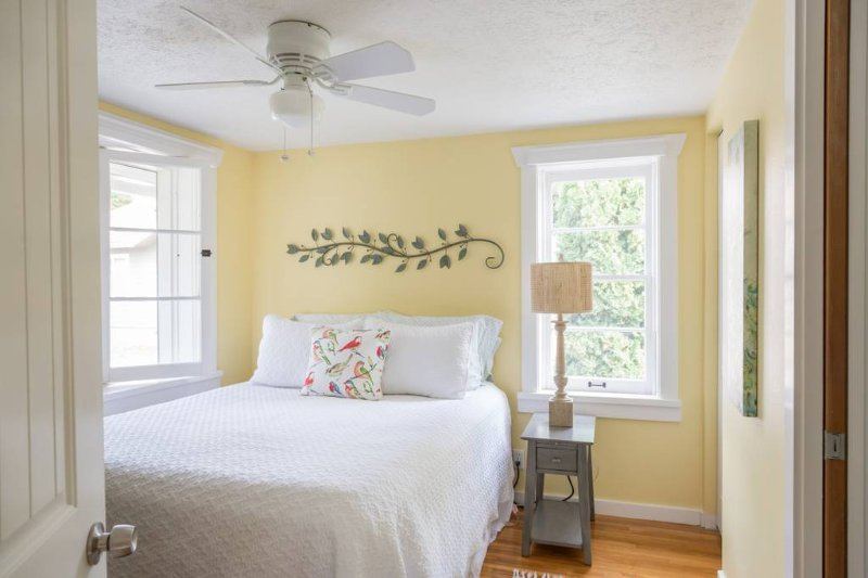 The master bedroom features a queen size bed, night stand with charging capabilities and a bathroom.
