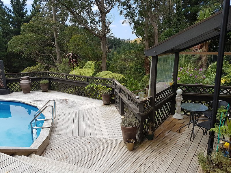 View from Gold Room of deck, garden and outside covered seating area.