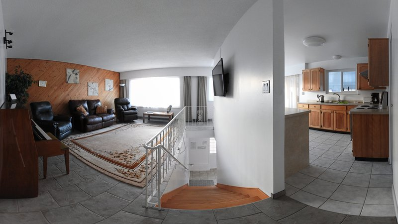 Panoramic shot of the living room, access stairwell and kitchen, taken from the hallway entrance.