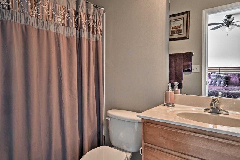 Chuveiro desligado no segundo quarto abastecido com toalhas.