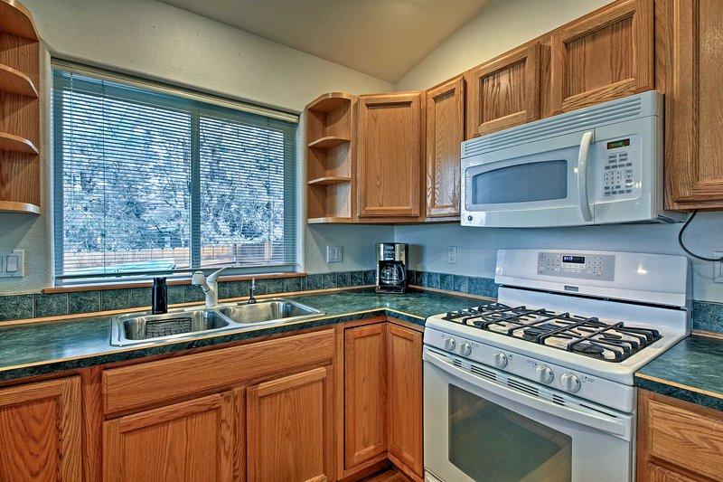 La cocina totalmente equipada con electrodomésticos modernos y un amplio venia bien.