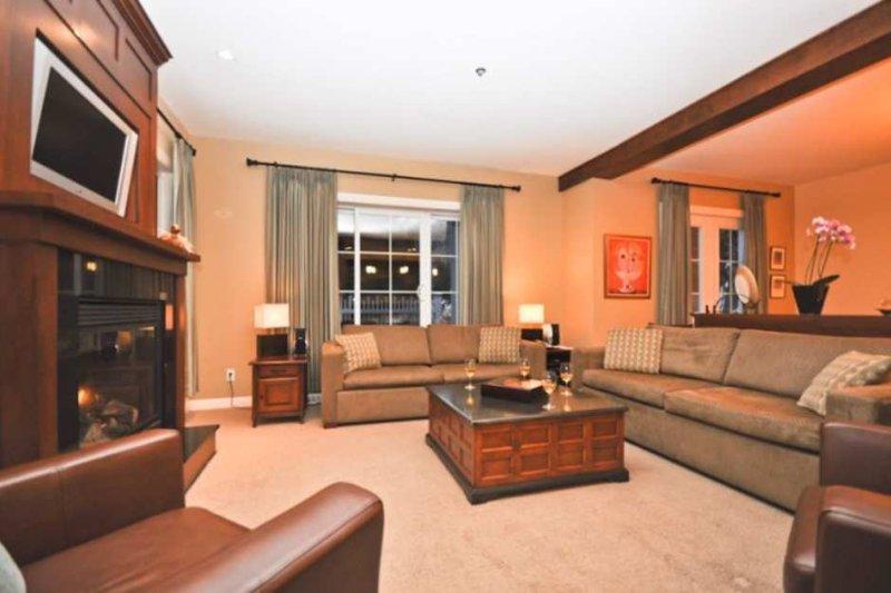 Das stilvolle Wohnzimmer verfügt über einen Flachbild-HDTV und einen Gaskamin