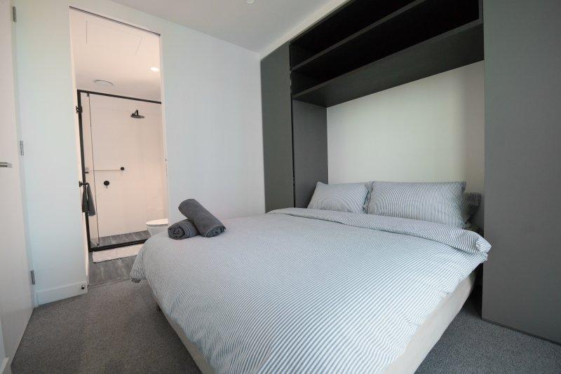 La chambre principale avec un grand lit et des oreillers moelleux.
