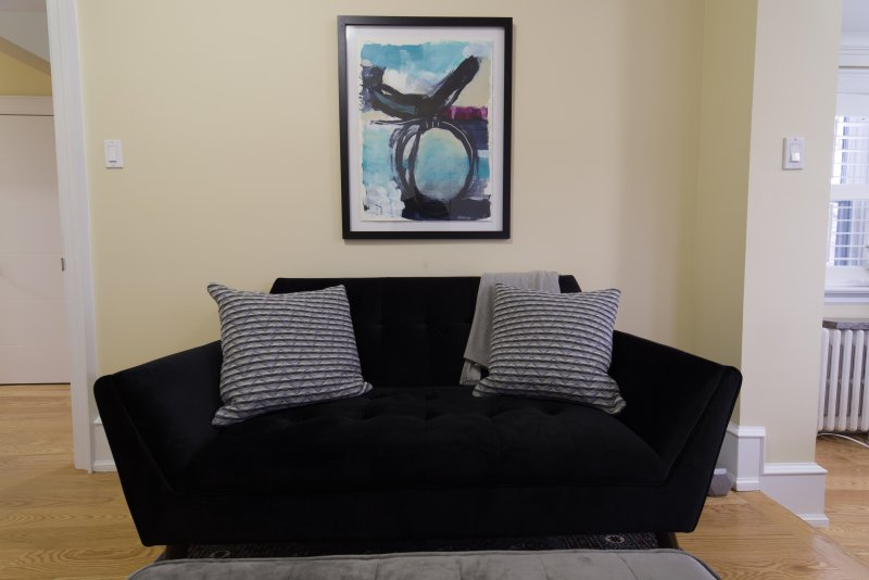 Plush love seat and modern art in bedroom 2 seating area.
