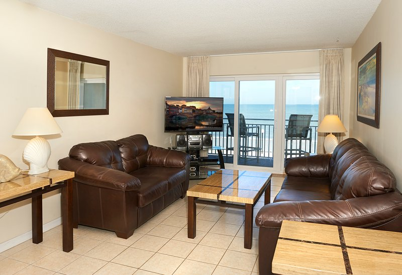 Living room with a direct ocean view, big screen TV and a sofa sleeper