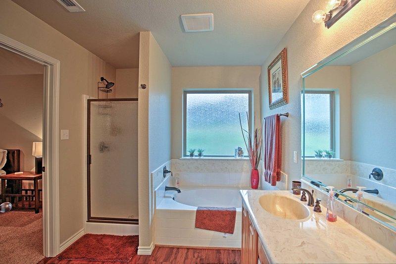 El baño principal incluye una tina de baño y ducha a ras de.