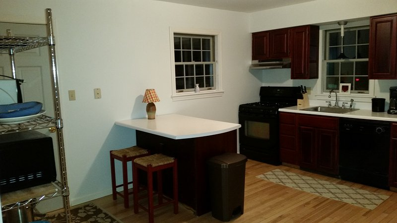 The main kitchen is fully equipped and has island and breakfast table seating