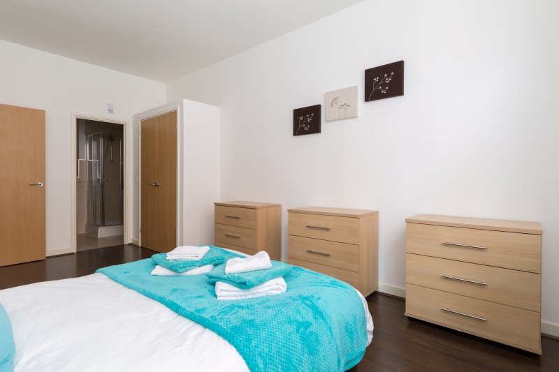 grote slaapkamer met een grote dubbele kledingkast, 3 grote lades en 2 nachtkastjes met lampen