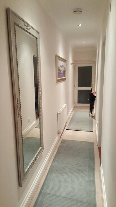 Bright hallway with beautiful full-length mirror, coat hooks, and umbrella rack.