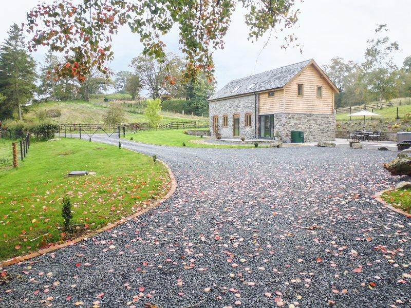 TYNDDOL BARN, exposed beams and stonework, hot tub, countryside views, Ref, holiday rental in Llaithddu
